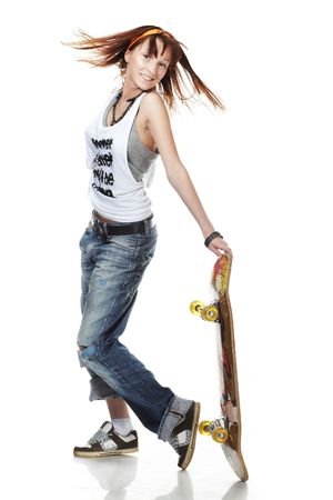 Portrait of smiling girl standing with skateboard on white background