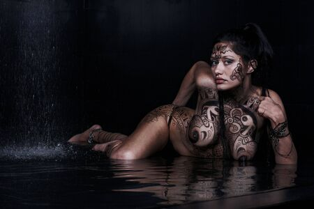 Beautiful model with bodypainting in water on black Stock Photo - 4919334