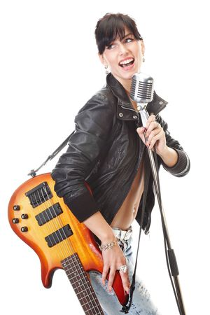Rock-n-roll girl holding a guitar singing into retro microphone isolated on white photo