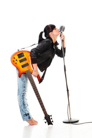 Rock-n-roll girl holding a guitar kissing retro microphone isolated on white photo