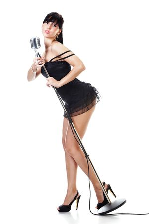 Sexy female singer wearing black dress holding a retro microphone isolated on white photo