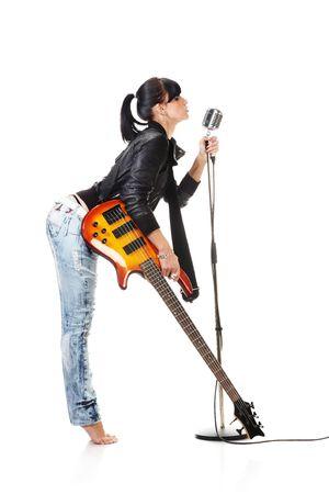 Rock-n-roll Mädchen mit einer Gitarre singend in Retro-Mikrofon isolated on white