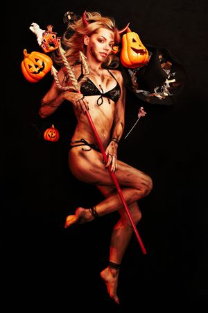 Beautiful devil with trident and Halloween accessories on black photo
