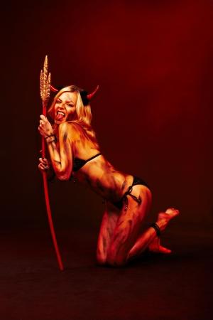 demonio: Beautiful vimpire diablo con tridente y accesorios de Halloween en rojo profundo negro Foto de archivo