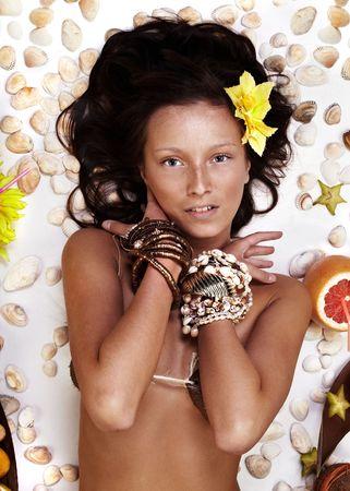 Beautiful exotic girl with Hawaiian accessories lying photo