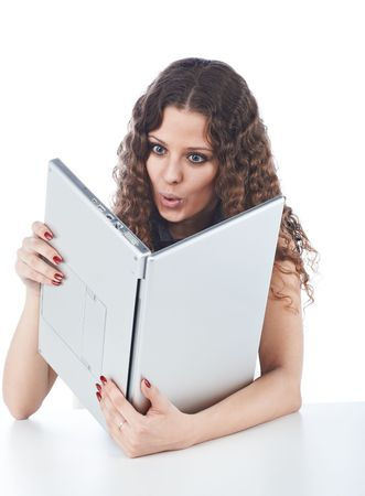 Beautiful young woman holding a laptop in improper way isolated on white photo
