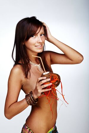 Beautiful exotic girl with Hawaiian accessories drinking coconut juice photo