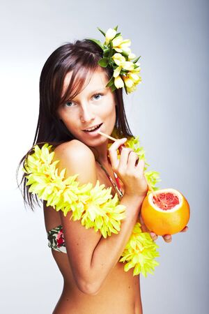 Beautiful exotic girl with Hawaiian accessories drinking grapefruit juice photo