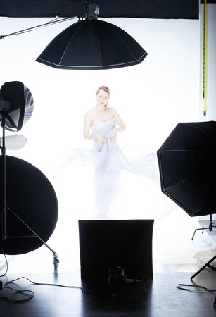 Young beautiful model posing in professionally equipped studio, waving by light fabric over white  photo