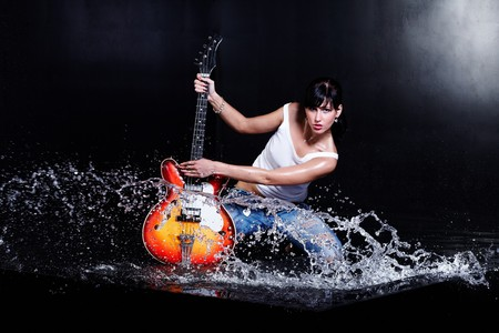 Rock-n-roll girl playing a guitar in water on black photo