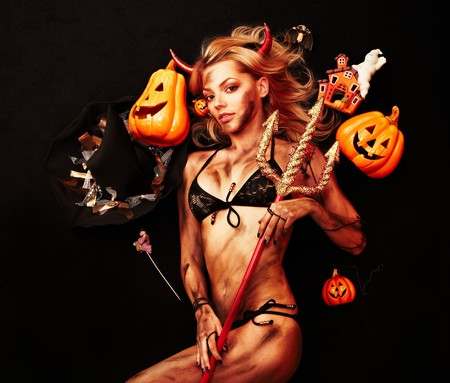 halloween witch: Beautiful devil with trident and Halloween accessories on black Stock Photo