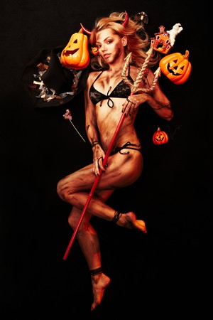 naughty girl: Beautiful devil with trident and Halloween accessories on black Stock Photo