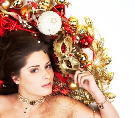 Beautiful brunette lying among Christmas decoration holding mask isolated on white photo