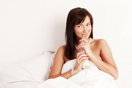 Young beautiful woman drinking milk sitting on white bed  photo