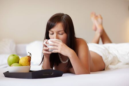 Young beautiful woman drinking coffee lying on white bed  photo