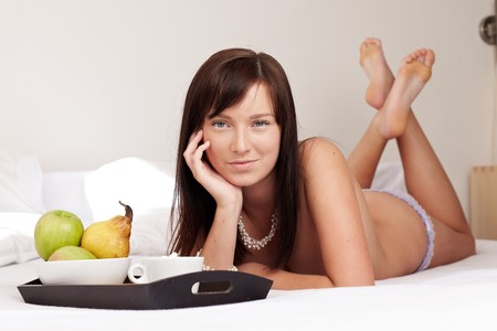 Young beautiful woman having breakfast lying on white bed  photo
