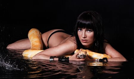 poison snakes: Beautiful woman lying with Python in water