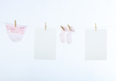 clean clothes: Two clean sheet of paper and baby?s clothes hanging on the clothesline