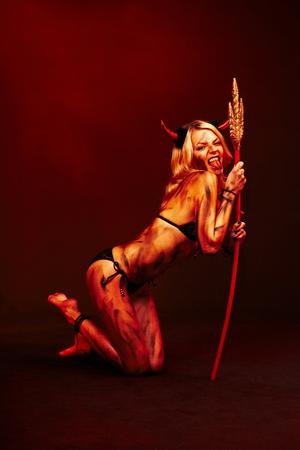 Mooie vampier duivel met drietand op diepe rode zwarte achtergrond
