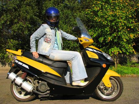 Girl in jeans sitting on the yellow moped