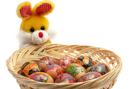 basket of easter eggs and toy rabbit on the white background