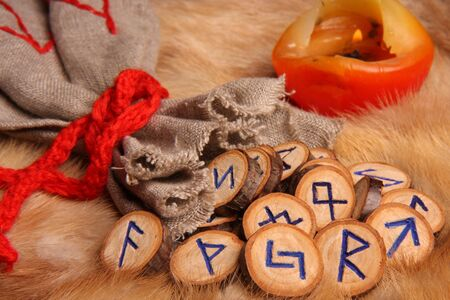 Runes with pouch and candle on the fur photo