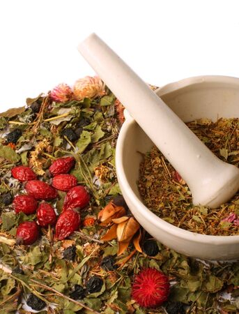 mortar with dry herbs and hips on white background