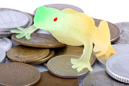 meanness: toy toad sitting on the old coins on white background Stock Photo