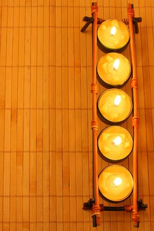 row of candles on bamboo rug Stock Photo - 3481327