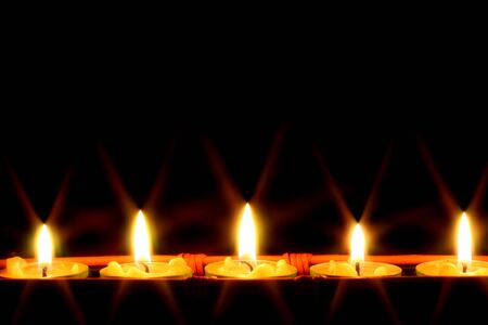 row of candles on black background photo