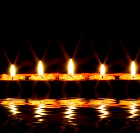 mirror on the water: Row of candles reflected in the water