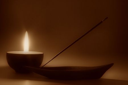 Still life with candle and incense stick, sepia toned photo