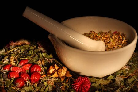 Mortar, dry herbs and hips isolated on black background photo
