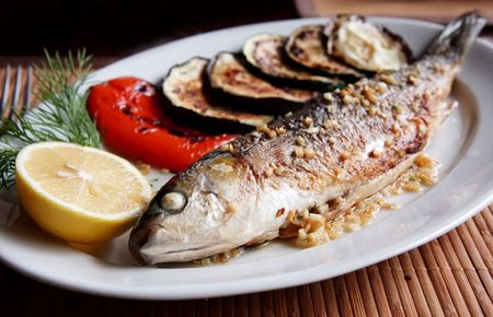 whole: Grilled fish (mullet) on plate. Shallow DOF.