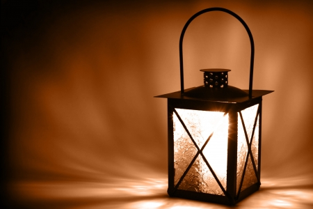 Lit lantern on dark background, sepia toned Stock Photo