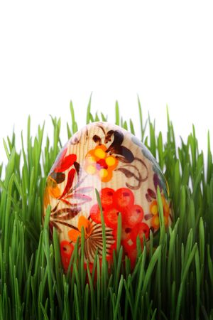 Easter egg in the grass isolated on white background photo