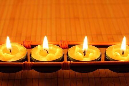 Row of candles on bamboo rug photo