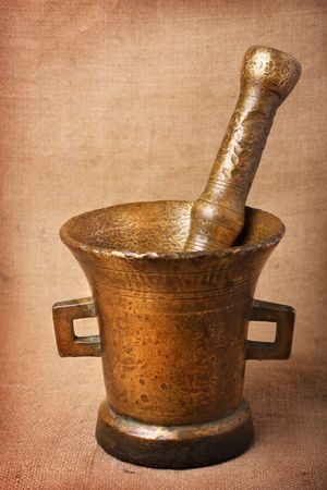 bronzy: Old bronze mortar and pestle on sacking background