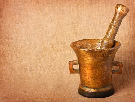 homoeopathic: Old bronze mortar and pestle on sacking background
