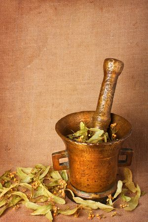 homoeopathic: Old bronze mortar with dry herbs on sacking background
