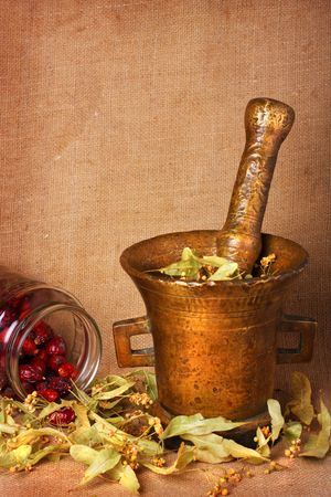 homoeopathic: Old bronze mortar with dry herbs and rose hips on sacking background