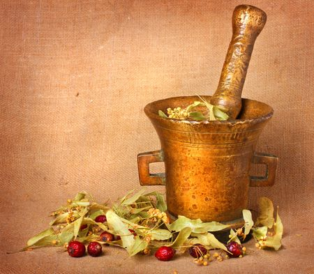 Old bronze mortar with linden and rose hips on sacking background photo