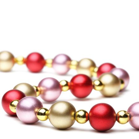 newyears: Christmas decoration of shining beads isolated on white. Shallow depth of field Stock Photo