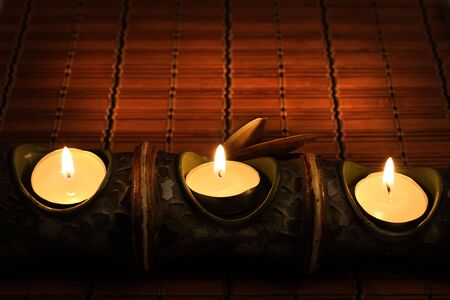 prayer rug: Candles on bamboo rug in the dark