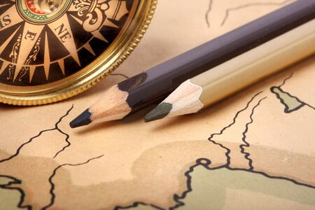 Compass and pencils on old contoured map, shallow DOF photo