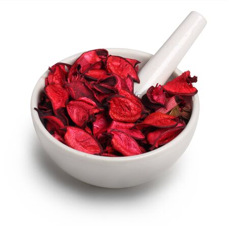 herbal remedy: Mortar and pestle with dry rose petals isolated on white background