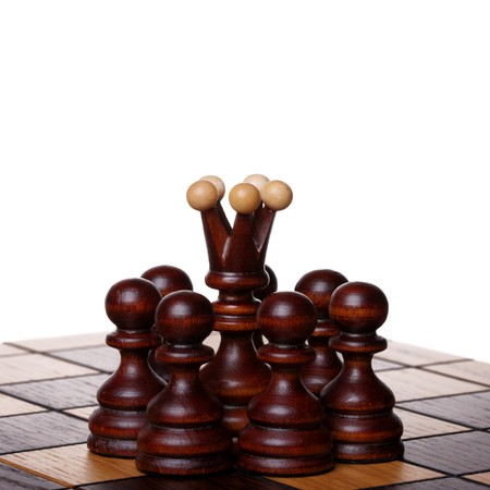 Black queen among pawns on a chess board. Isolated on white Stock Photo - 8133792