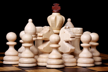 White wooden chess pieces on a chess board. Isolated on black photo
