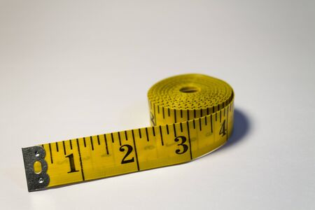 Yellow measuring tape on white background photo