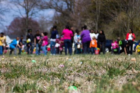 dozens: Dozens of children line up to participate in an Easter Egg Hunt in an open field.